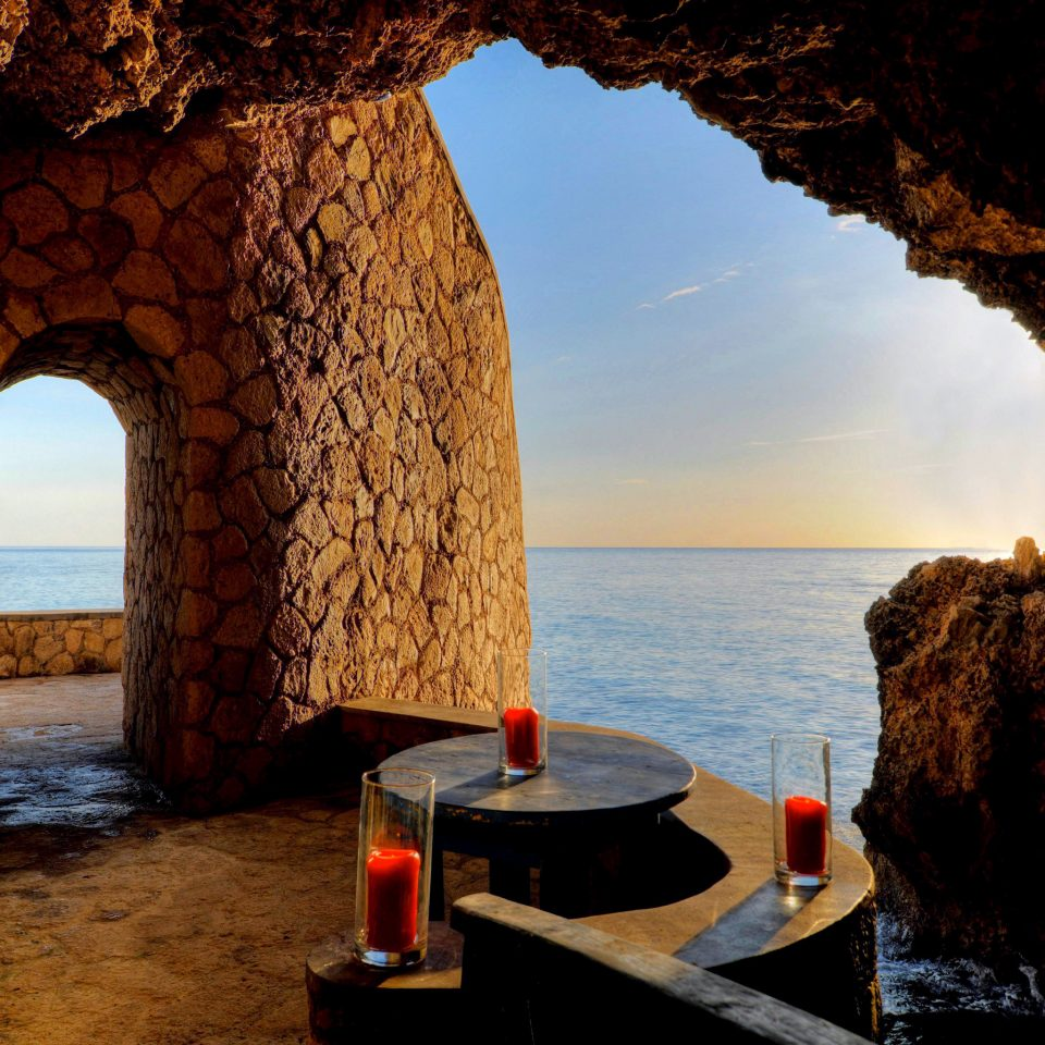 Dining Drink Eat Hotels Luxury Romance Romantic Scenic views Trip Ideas Tropical Waterfront water building mountain arch Sea evening overlooking formation