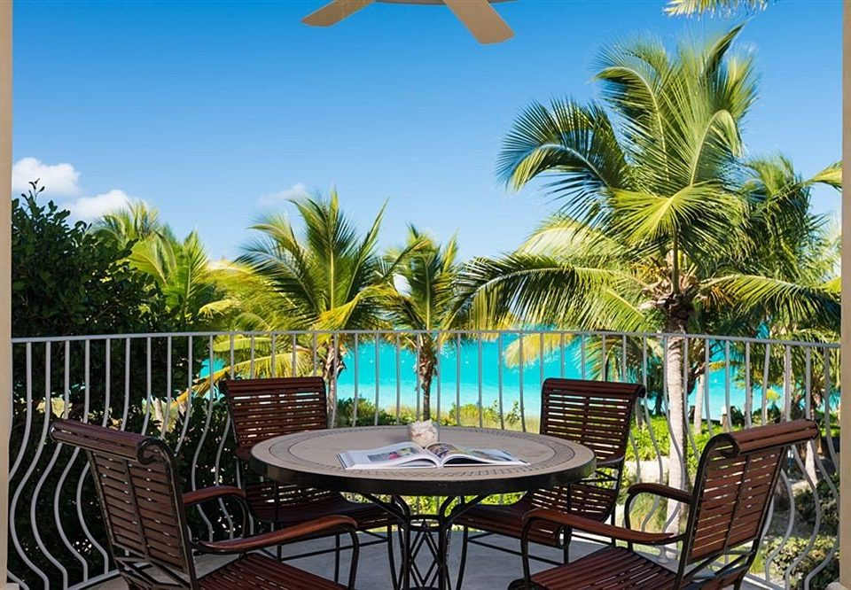 tree sky chair umbrella palm leisure property caribbean Resort Dining lawn arecales home swimming pool Villa backyard condominium plant Garden colorful shade dining table
