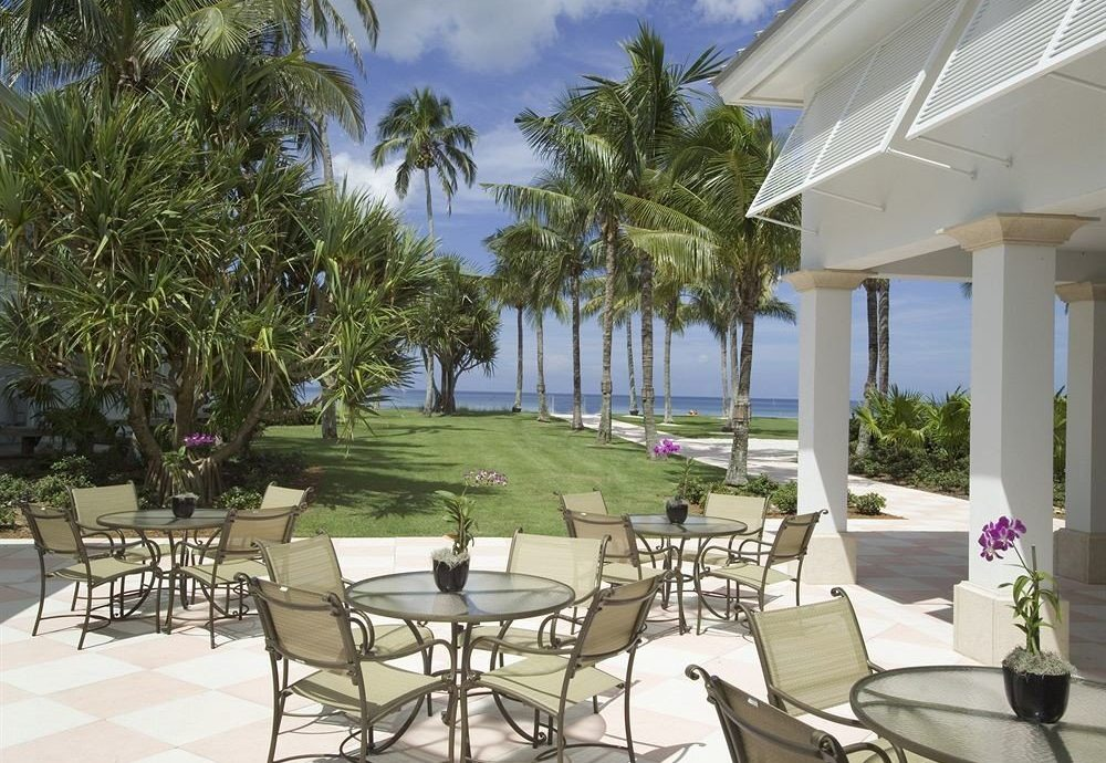 Dining Outdoors Patio Waterfront tree chair property Resort Villa porch condominium home lawn caribbean backyard restaurant mansion cottage palm lined set arranged