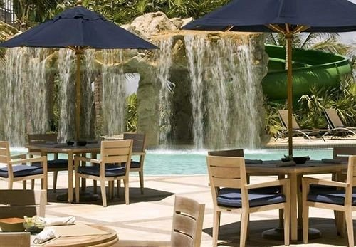 chair property Dining gazebo Resort cottage Villa outdoor structure backyard swimming pool set surrounded dining table