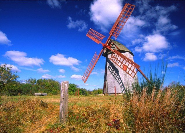 sky grass windmill mill wind turbine sign wind farm prairie wind machine energy outdoor object