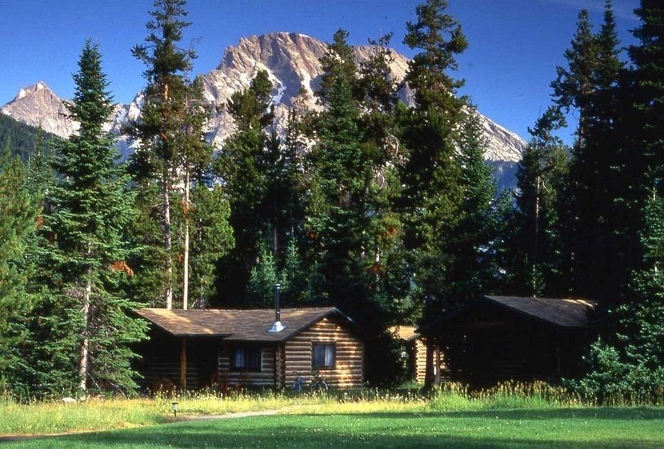 Exterior Lodge Mountains Romantic tree grass wilderness hut log cabin woodland meadow mountain range mountain cottage plant Forest lush surrounded wooded hillside