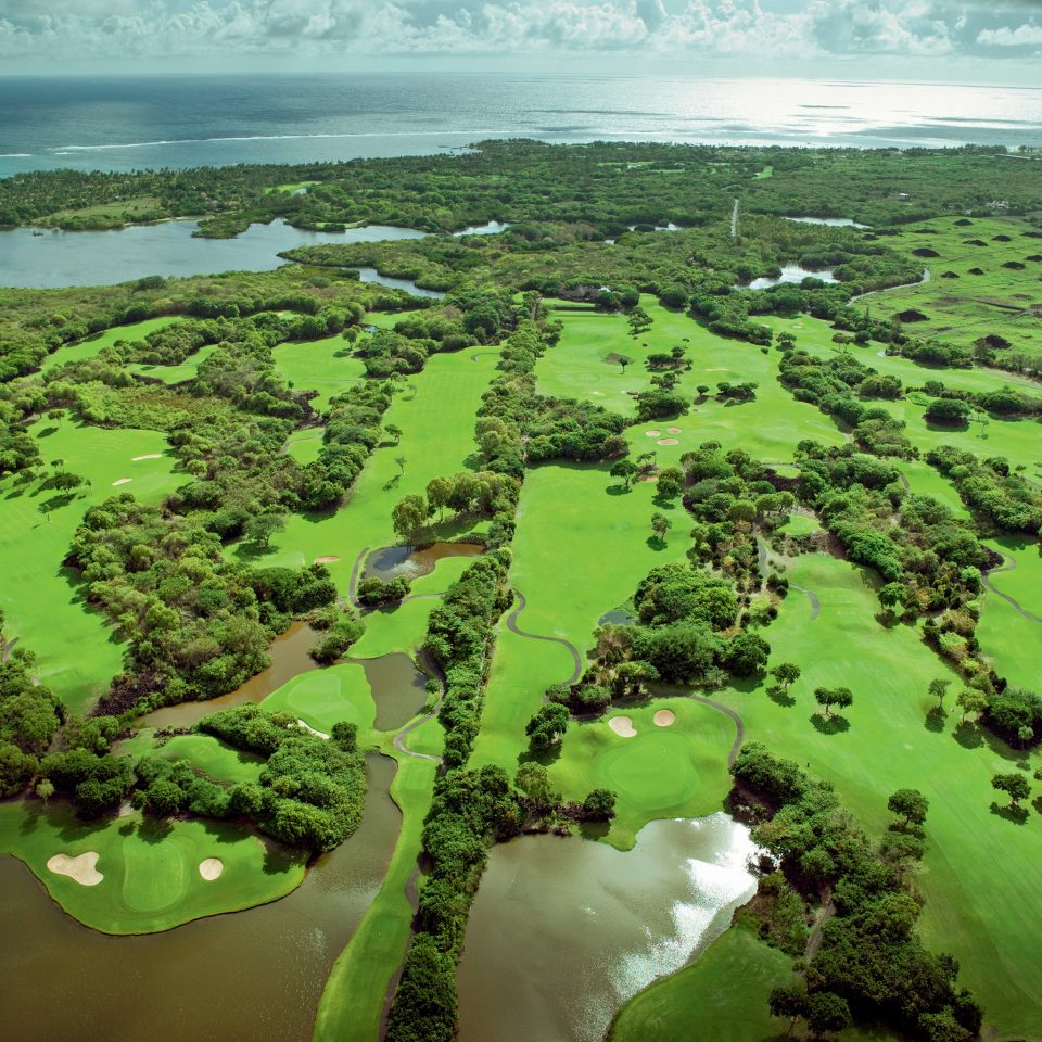 Family Golf Romantic Tropical Waterfront grass aerial photography habitat bird's eye view vegetation plain green structure Nature natural environment ecosystem grassland field atmosphere of earth wetland sport venue hill landscape soil rural area plateau Jungle biome golf course lush