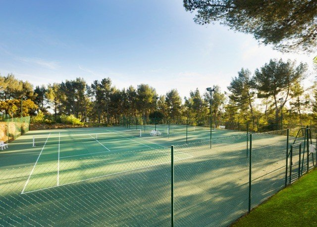 tree Sport sky athletic game tennis structure property sport venue grass baseball field lawn residential area stadium Fence