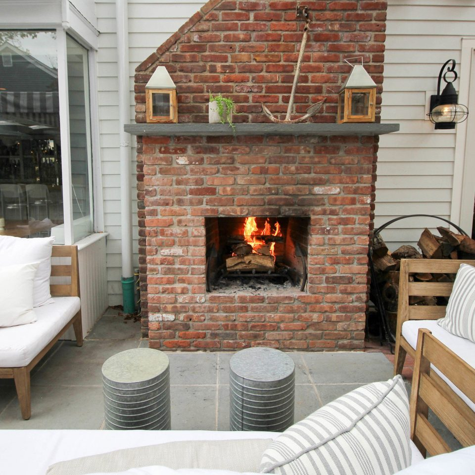 Fireplace sofa fire property living room home hearth cottage brick porch outdoor structure farmhouse stone