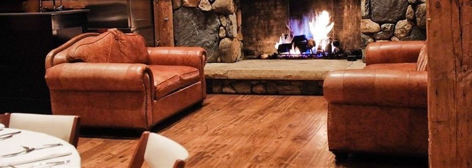 sofa man made object Fireplace living room hardwood leather home stone wood flooring cottage seat