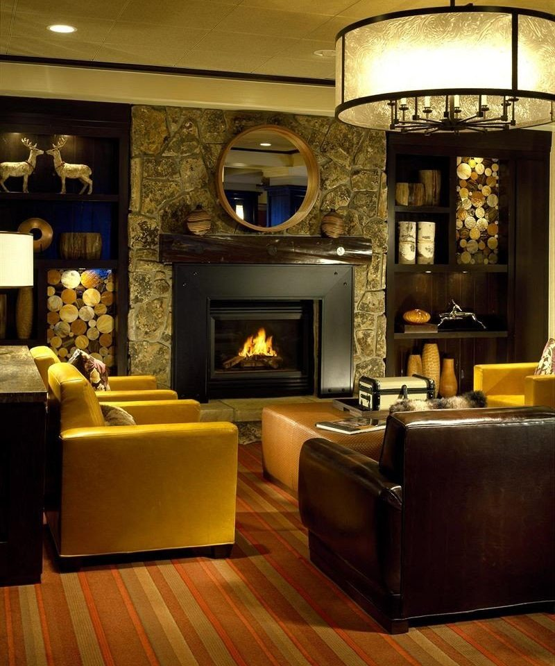 Fireplace Lounge Resort living room Lobby recreation room hardwood home lighting Suite wood flooring flooring