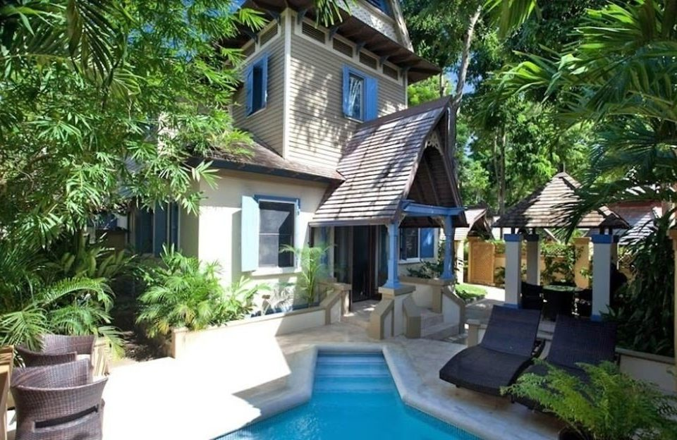 tree property Resort building plant Villa swimming pool cottage condominium home backyard eco hotel Garden Jungle house palm stone bushes