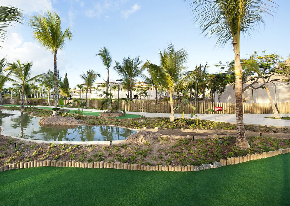 grass sky tree palm structure plant Resort swimming pool sport venue arecales lawn walkway golf course palm family Garden