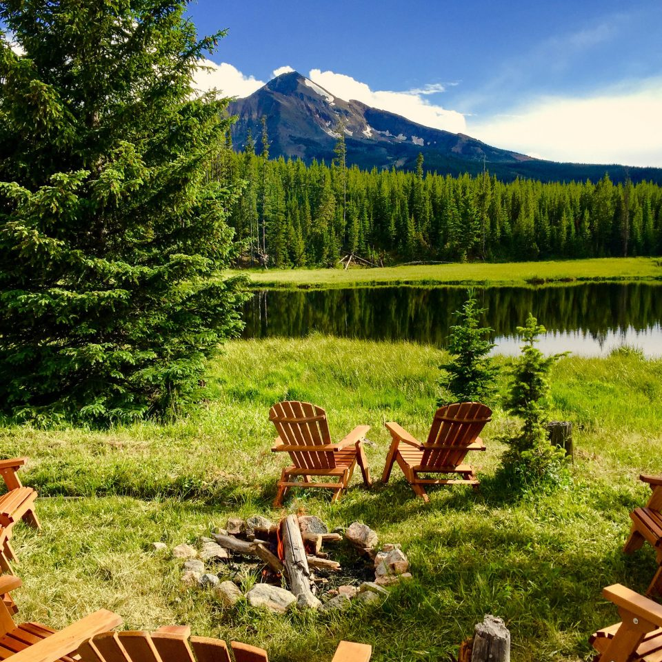 Glamping Hotels Montana Outdoors + Adventure Trip Ideas Nature wilderness nature reserve ecosystem national park mountain Lake mount scenery biome landscape tree meadow grass mountain range log cabin