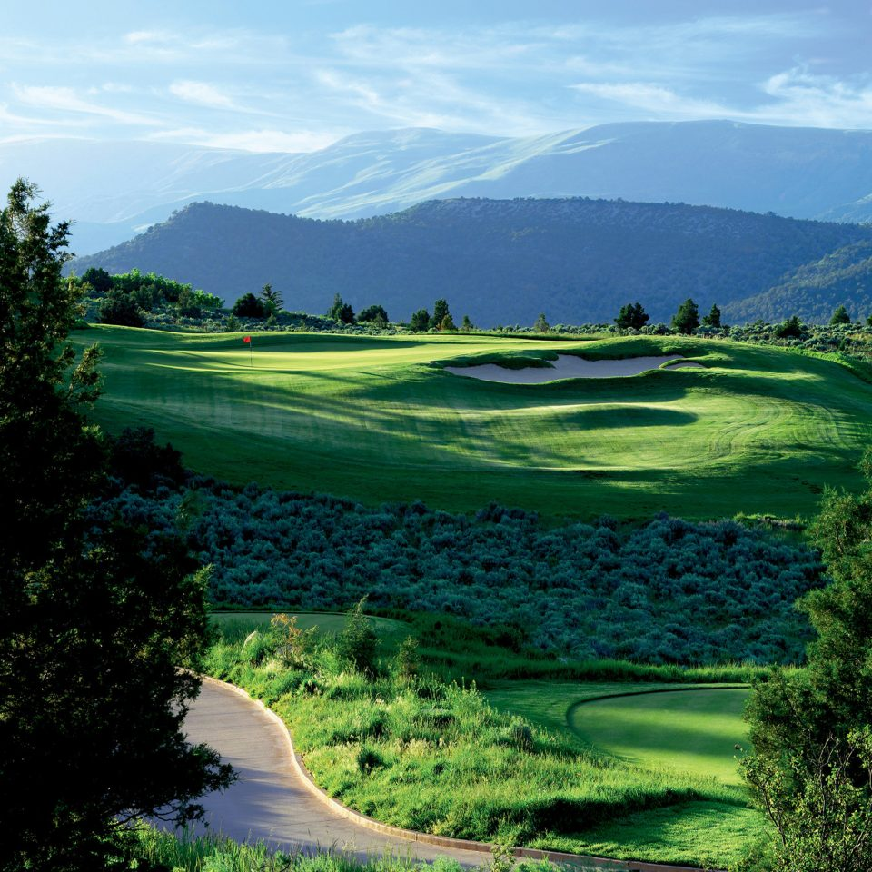 grass tree mountain sky structure green sport venue Nature grassland golf course Golf sports golf club hill outdoor recreation recreation Lake overlooking lush surrounded highland