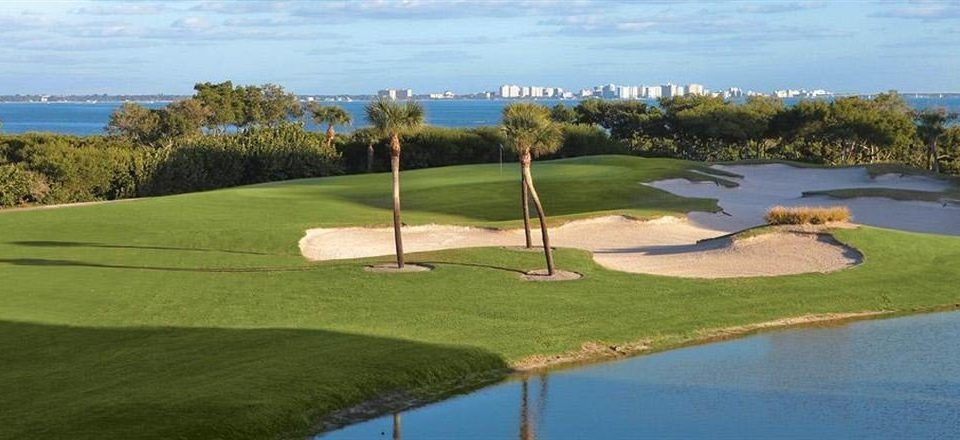 grass sky water structure sport venue pitch and putt Golf golf course River sports golf club outdoor recreation baseball field grassland recreation Lake overlooking lush