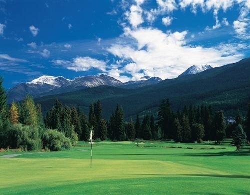 grass sky mountain tree athletic game structure Sport Golf sport venue field grassland mountain range golf course sports outdoor recreation green golf club meadow pasture recreation lush distance