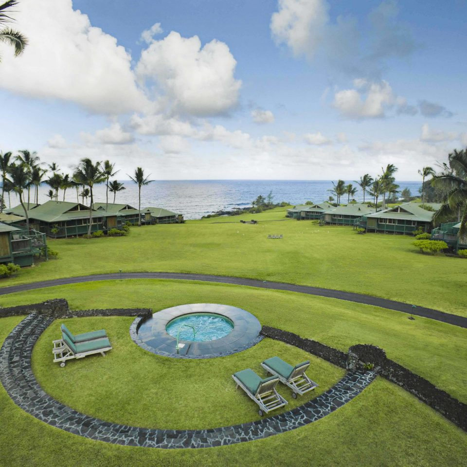 Grounds Hot tub Hotels Outdoor Activities Outdoors Play Rustic Waterfront grass sky tree structure sport venue residential area lawn golf course arecales golf club Resort plant aerial photography stadium grassy lush day