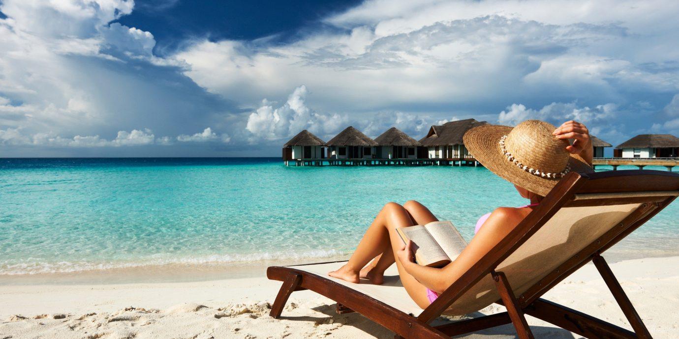 Arts + Culture sky outdoor chair water leisure Sea Beach shore vacation Ocean caribbean Coast sitting sand bay day