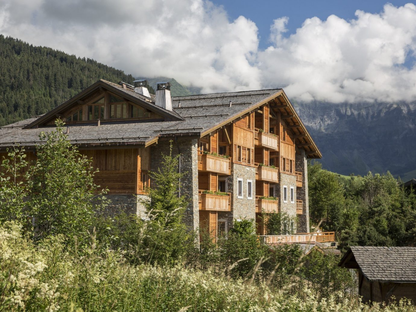 Boutique Hotels Hotels Outdoors + Adventure Winter outdoor building tree sky house grass mountainous landforms mountain home hut mountain range cottage mountain village alps farmhouse log cabin real estate rural area roof facade estate elevation landscape Villa Village hillside
