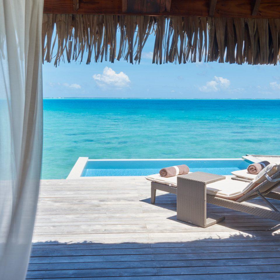 chair blue Sea property caribbean Ocean swimming pool Resort water window treatment sky shade Honeymoon amenity leisure lawn tropics overlooking set
