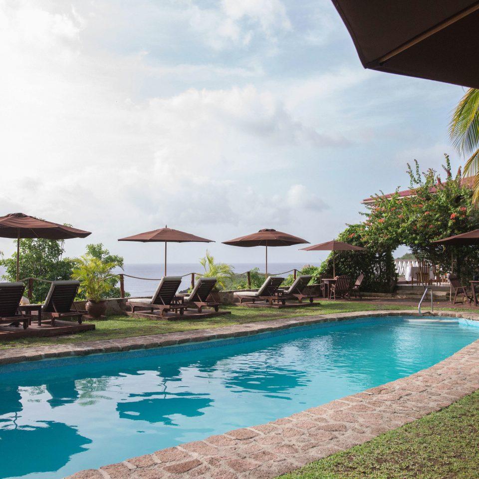 Hotels sky umbrella grass water Resort swimming pool Pool property leisure lawn Villa condominium swimming caribbean blue day