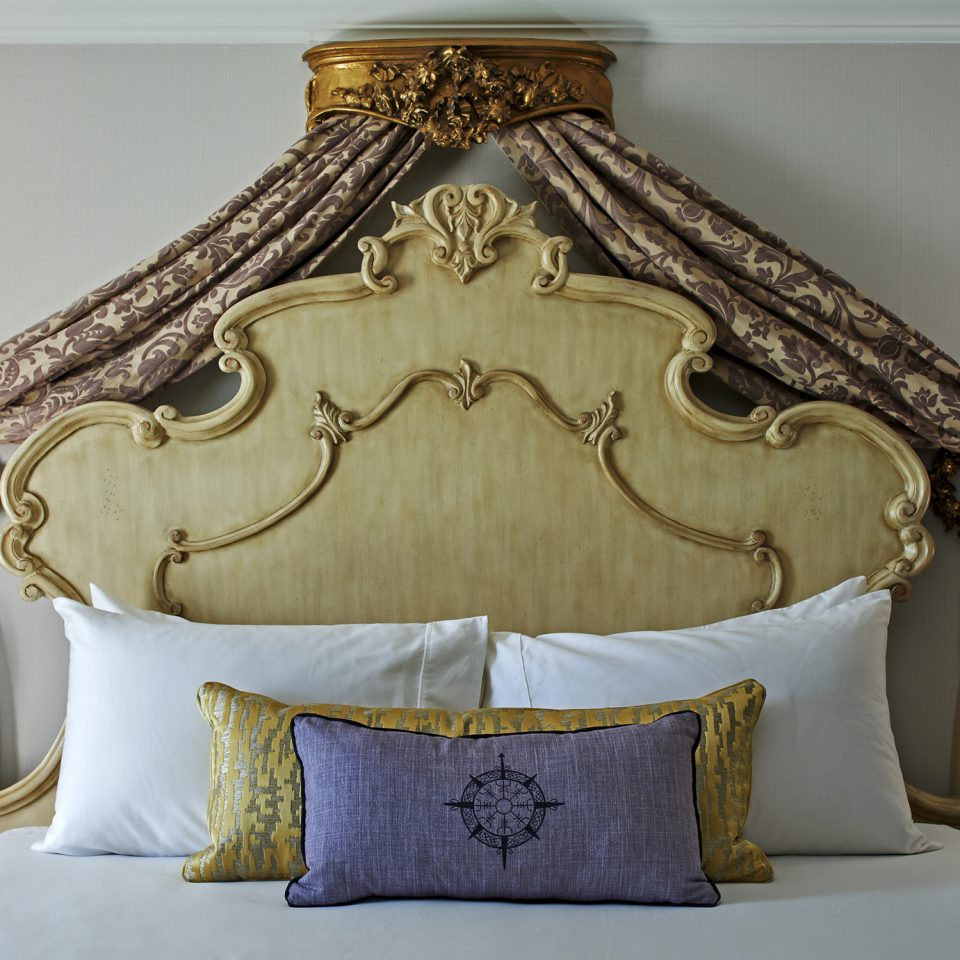 Frontal closeup of bed with gold and purple accents