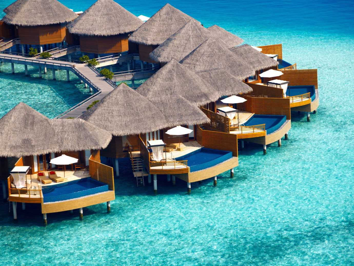 Beachfront Elegant Hotels Living Lounge Luxury Ocean Overwater Bungalow table water floor chair umbrella leisure blue Sea swimming pool vacation Resort Beach caribbean vehicle dock Harbor bay marina Water park Island swimming