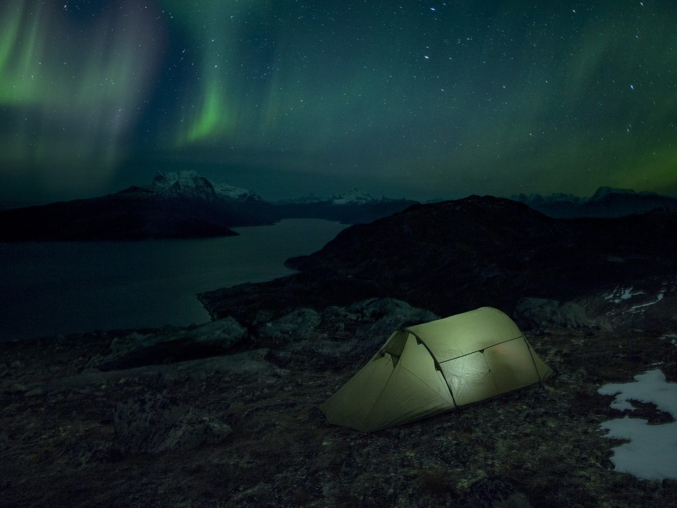 A tent pitched under the Northern Lights with a view of Sermitsiaq Moutain (near Nuuk)