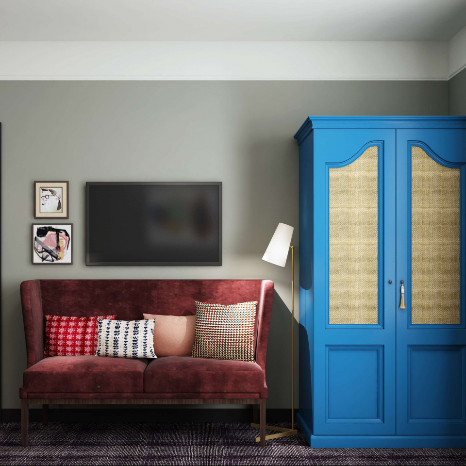 Red velvet couch and electric blue wardrobe against a wall