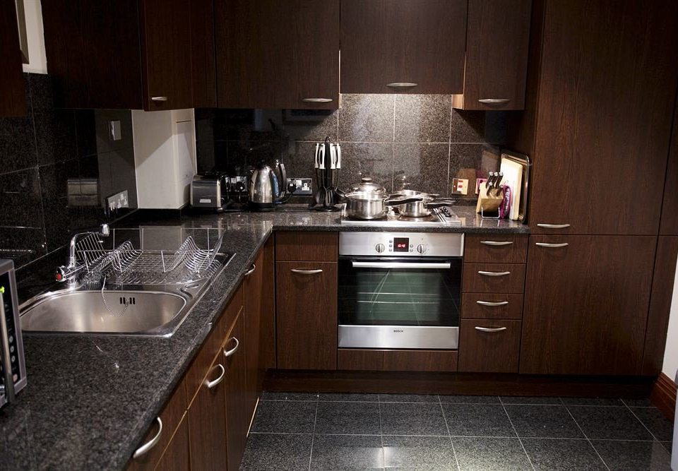 Kitchen cabinet property countertop counter cabinetry home appliance stove cottage cuisine stainless steel kitchen appliance tile Island