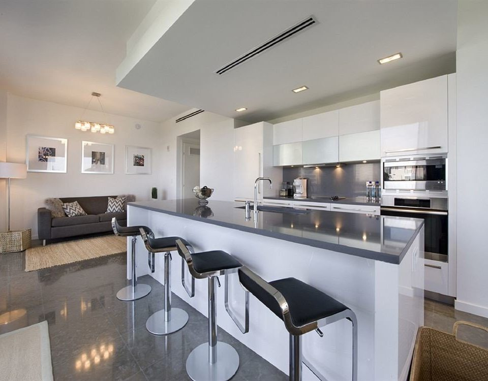Kitchen property counter countertop condominium lighting home cuisine cabinetry loft stainless appliance Island kitchen appliance