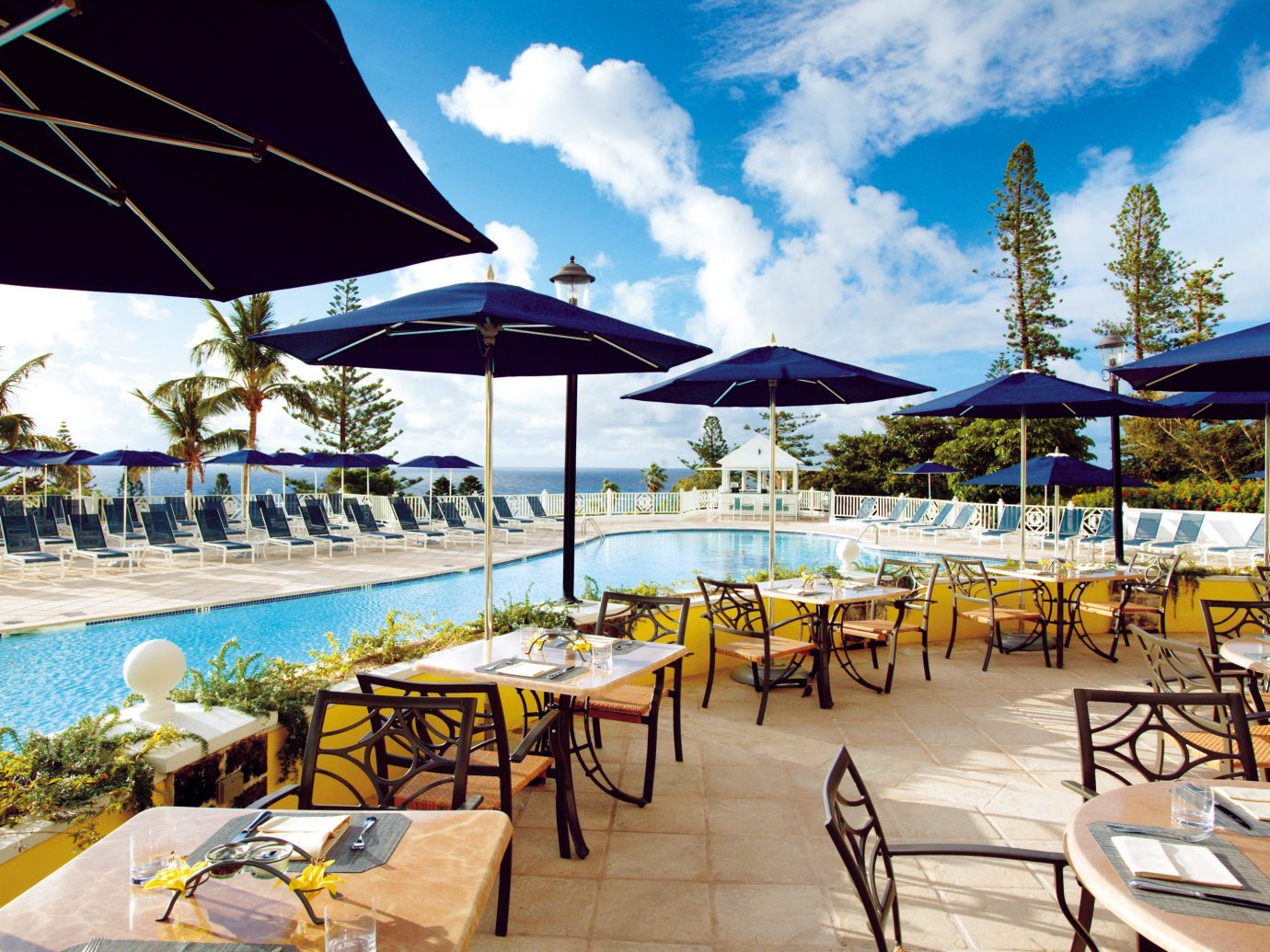 Beachfront Dining Drink Eat Hotels Play Pool sky umbrella chair outdoor table leisure lawn Resort vacation restaurant tourism estate Beach set caribbean furniture several shade swimming