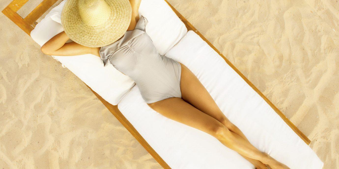 Travel Tips indoor footwear leg bed furniture shoe wood hand textile human body beige