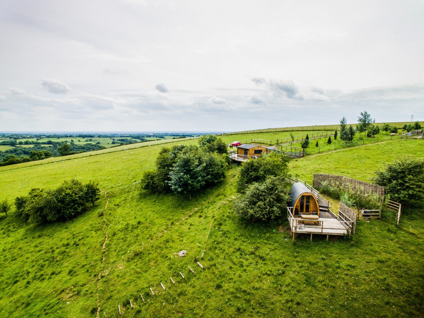 Glamping Outdoors + Adventure Trip Ideas grass sky outdoor field grassland green pasture Farm vegetation prairie hill rural area meadow plain tree grassy cloud landscape agriculture lush land lot hill station ecoregion steppe plant shrubland Village plantation plant community crop hillside highland