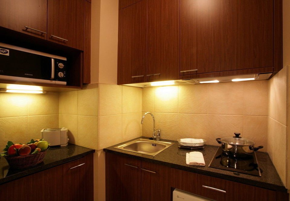 cabinet Kitchen property cabinetry home counter hardwood lighting countertop appliance