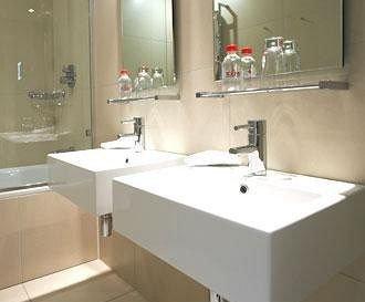 bathroom sink property countertop white Kitchen plumbing fixture flooring tan tile tiled
