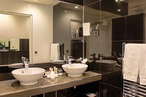 bathroom sink mirror property lighting home Kitchen countertop Suite condominium living room Modern tub