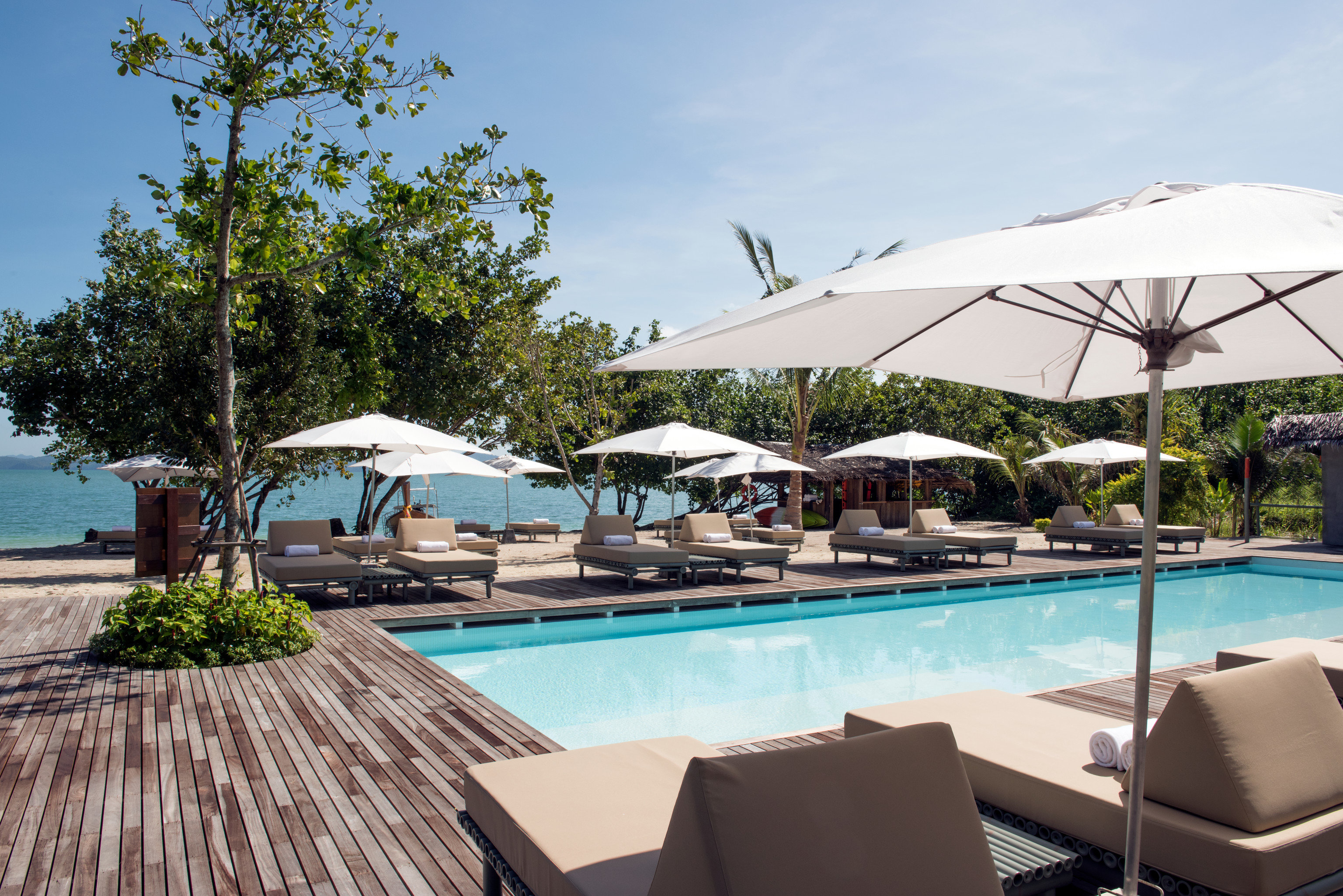 Beach Hotels Phuket Thailand sky outdoor tree umbrella Resort swimming pool property leisure vacation real estate hotel tourism resort town estate shade Villa outdoor structure water amenity open set furniture day several