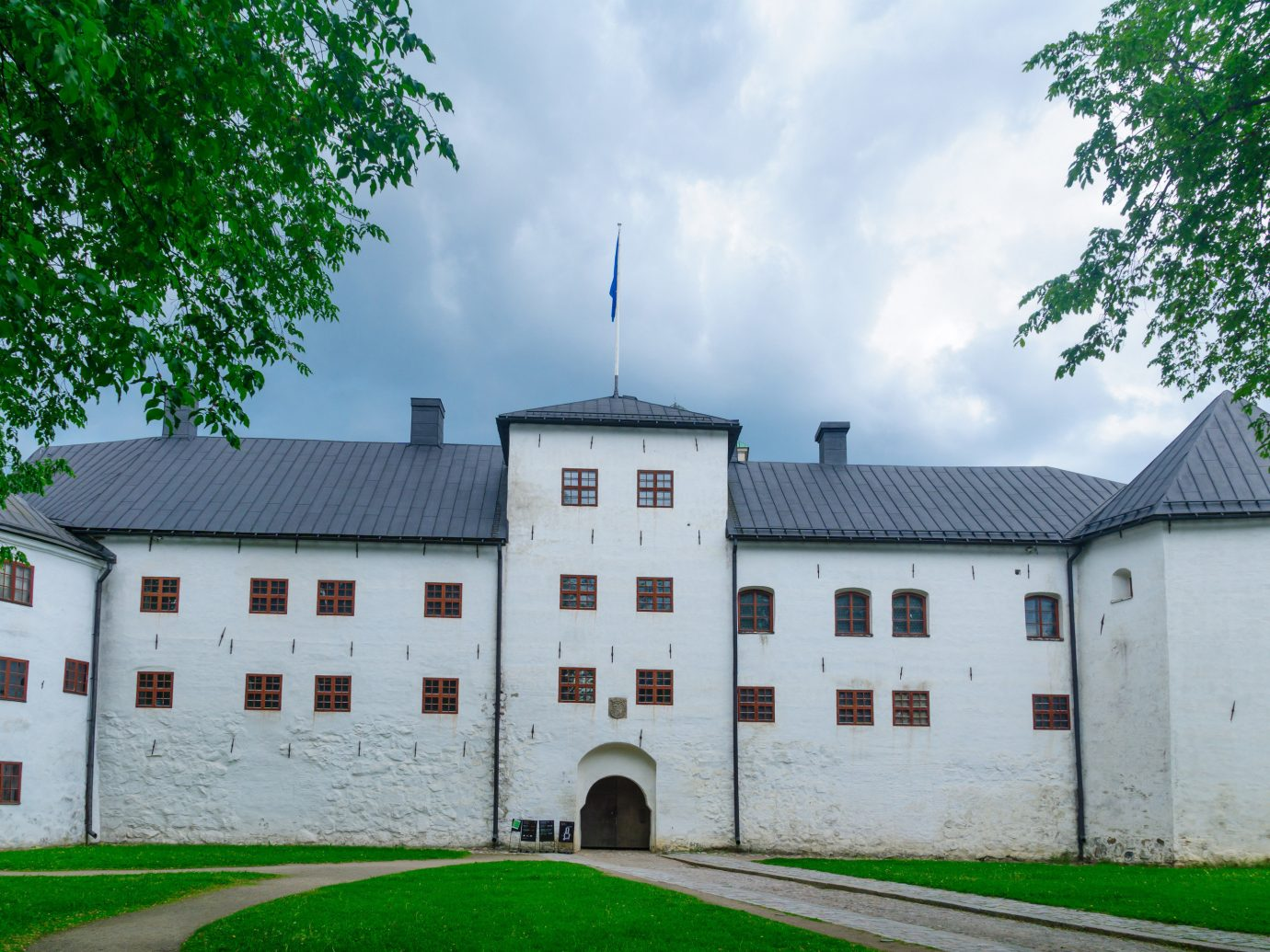 Finland Trip Ideas tree outdoor grass building sky house château estate property manor house facade stately home mansion castle medieval architecture national trust for places of historic interest or natural beauty palace window almshouse abbey residential roof old
