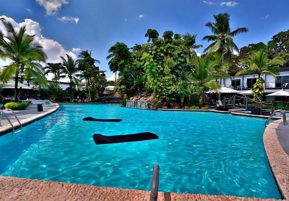 tree sky water Resort swimming pool property Pool leisure caribbean Lagoon Villa resort town condominium Sea palm blue lined swimming surrounded day