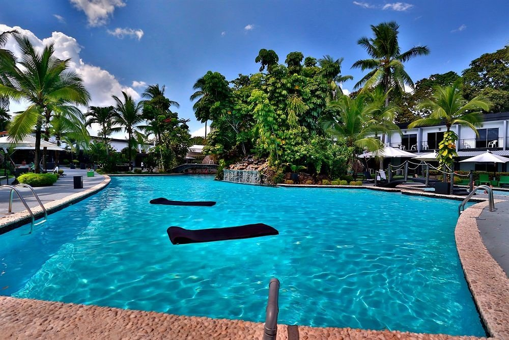 tree sky water Resort swimming pool property Pool leisure caribbean Lagoon Villa resort town condominium Sea palm blue lined swimming surrounded day