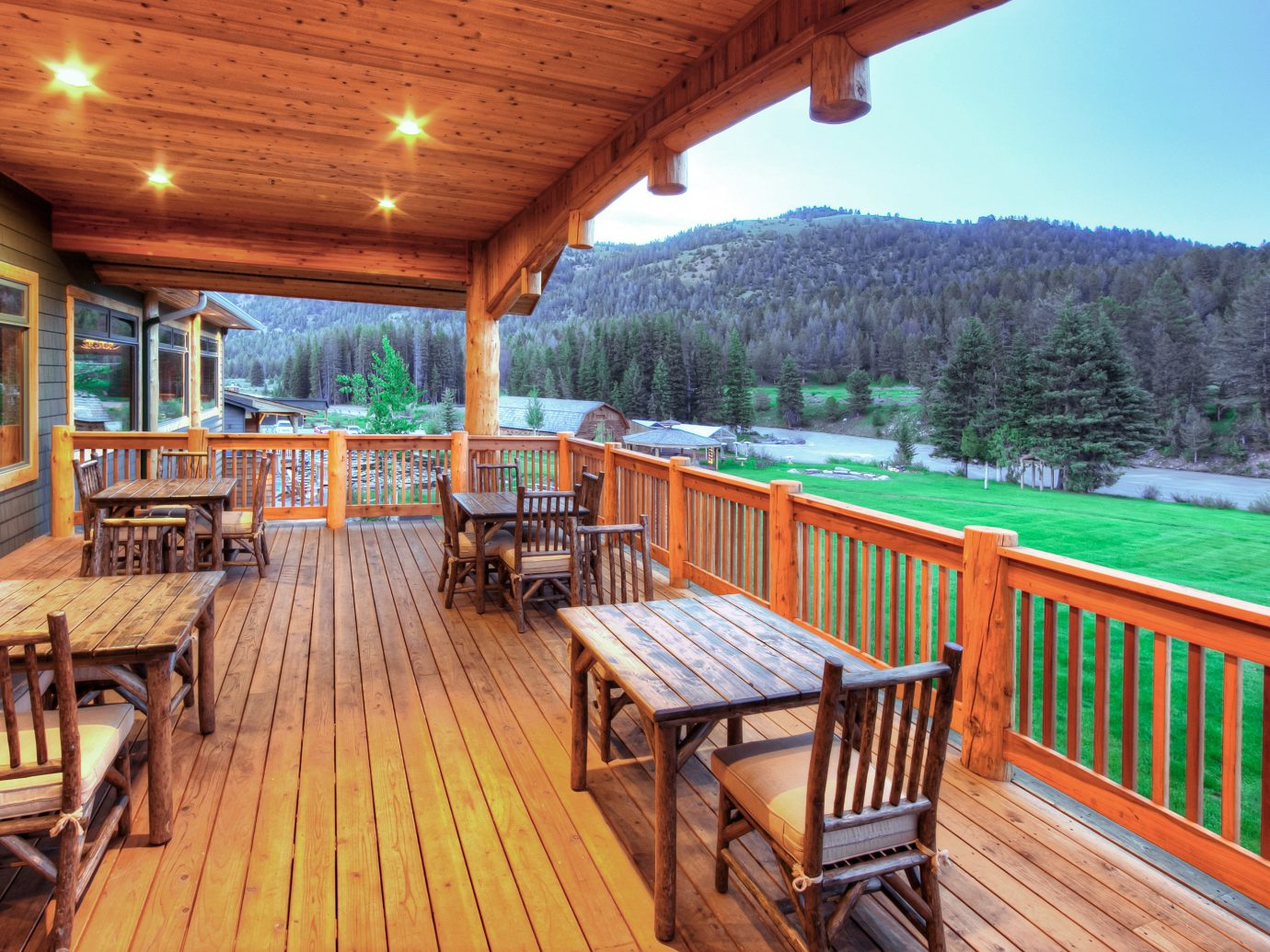 Country Deck Glamping Hotels Lodge Montana Outdoors + Adventure Patio Ranch Rustic Scenic views Trip Ideas wooden chair outdoor building property estate Resort cottage real estate outdoor structure Villa porch log cabin eco hotel wood area furniture