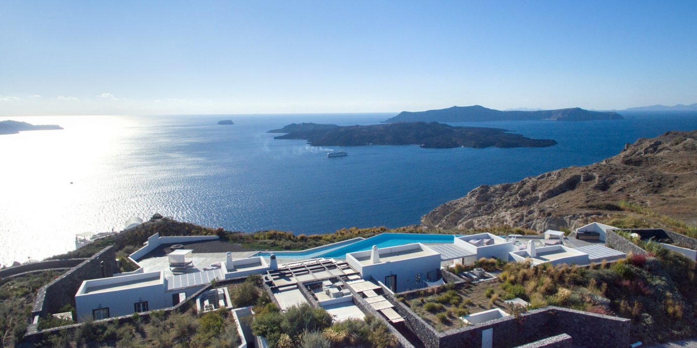 Greece Hotels Santorini Trip Ideas sky outdoor Nature Sea mountain water Coast coastal and oceanic landforms real estate bay aerial photography promontory horizon tourism Ocean travel house City overlooking hillside