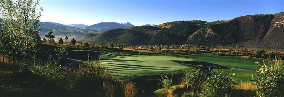grass sky Nature mountain mountainous landforms structure green sport venue hill mountain range valley landscape golf course plateau sports panorama grassy lush overlooking hillside highland