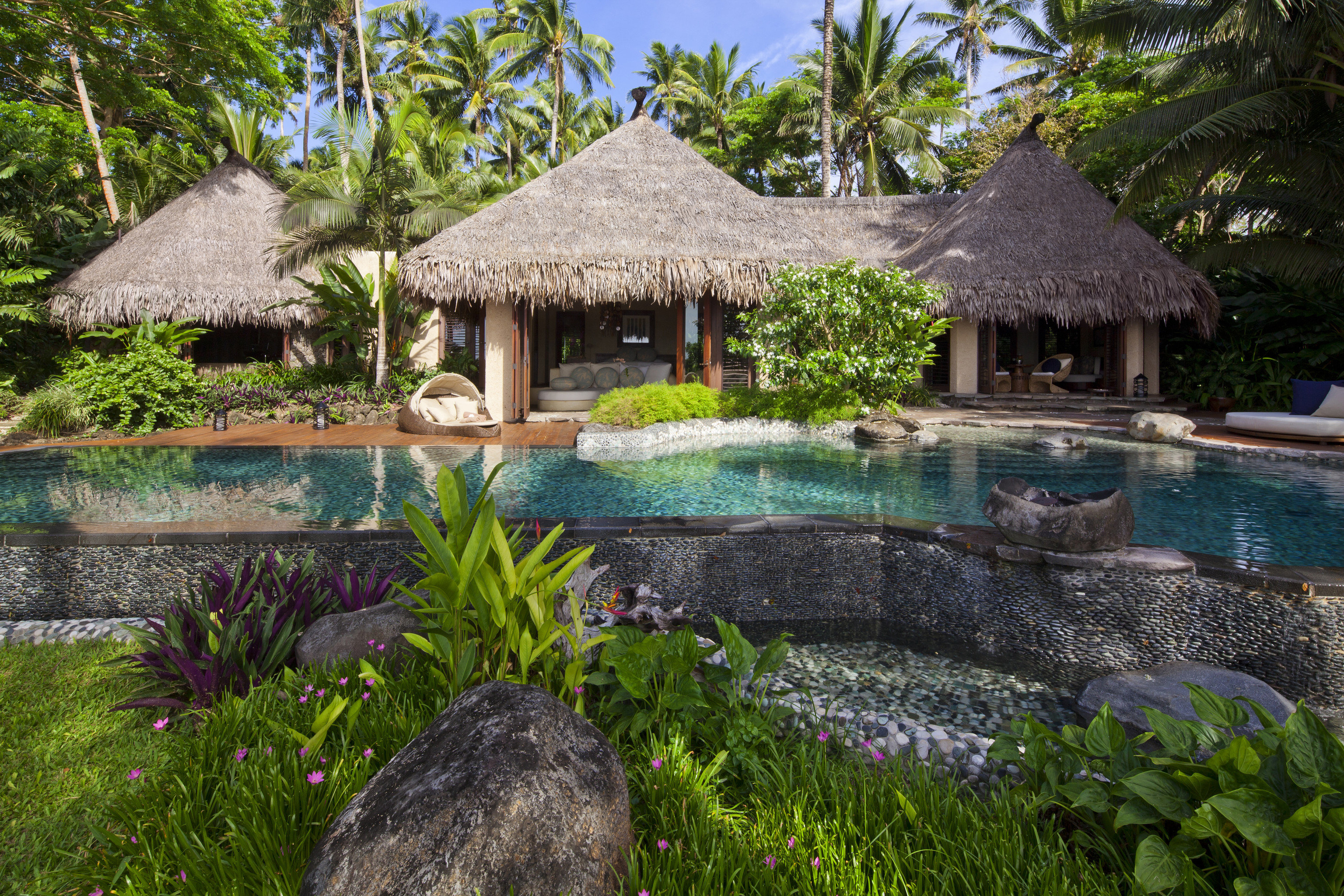 All-Inclusive Resorts Boutique Hotels Hotels Romance outdoor tree grass rock Resort house swimming pool building arecales water leisure palm tree plant tropics estate cottage real estate Garden reflection hacienda landscape Villa outdoor structure Jungle landscaping lawn hut stone area surrounded
