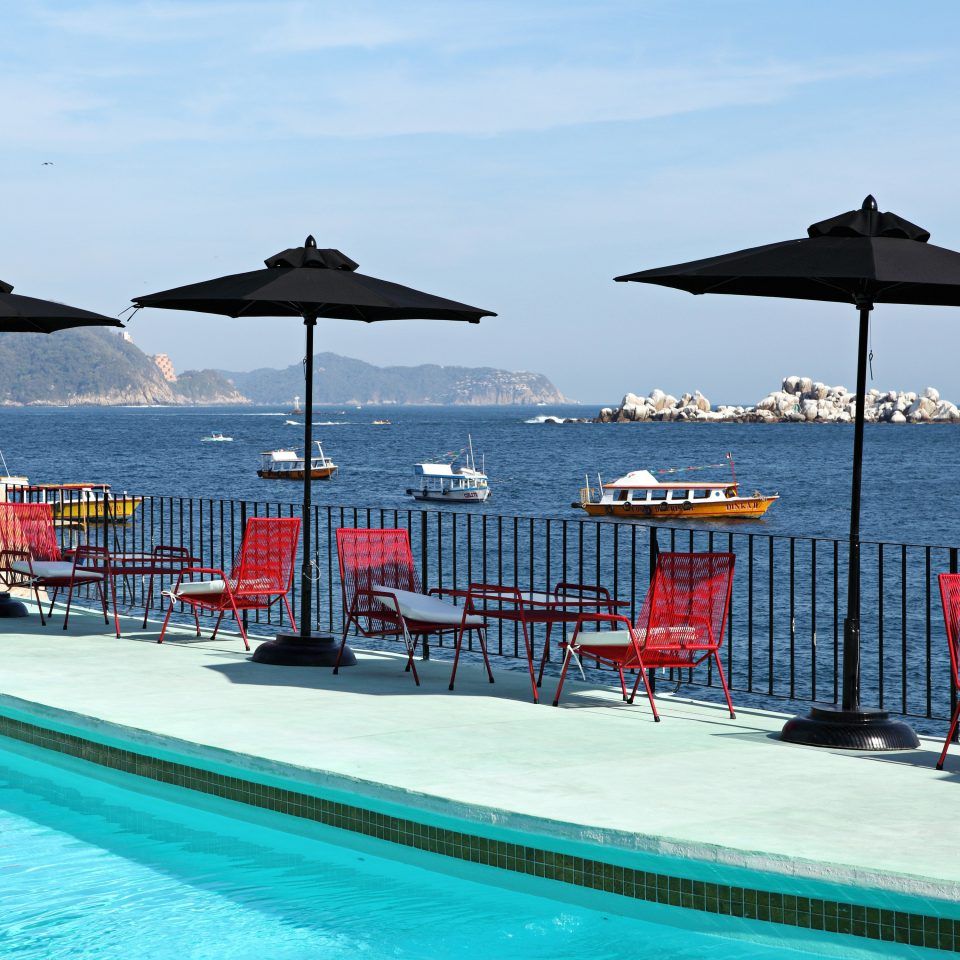 Patio Pool Resort Waterfront water sky umbrella chair ground swimming Sea lawn Ocean blue vehicle swimming pool lined day sandy