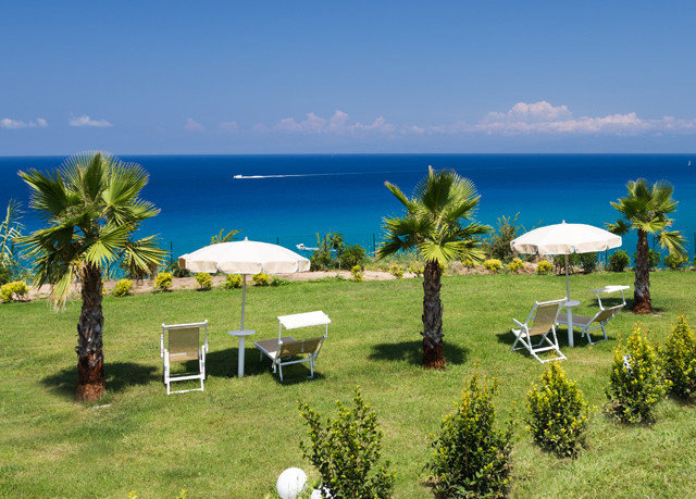 grass sky water umbrella property Resort lawn Ocean Villa caribbean home hacienda overlooking arecales shore lush day