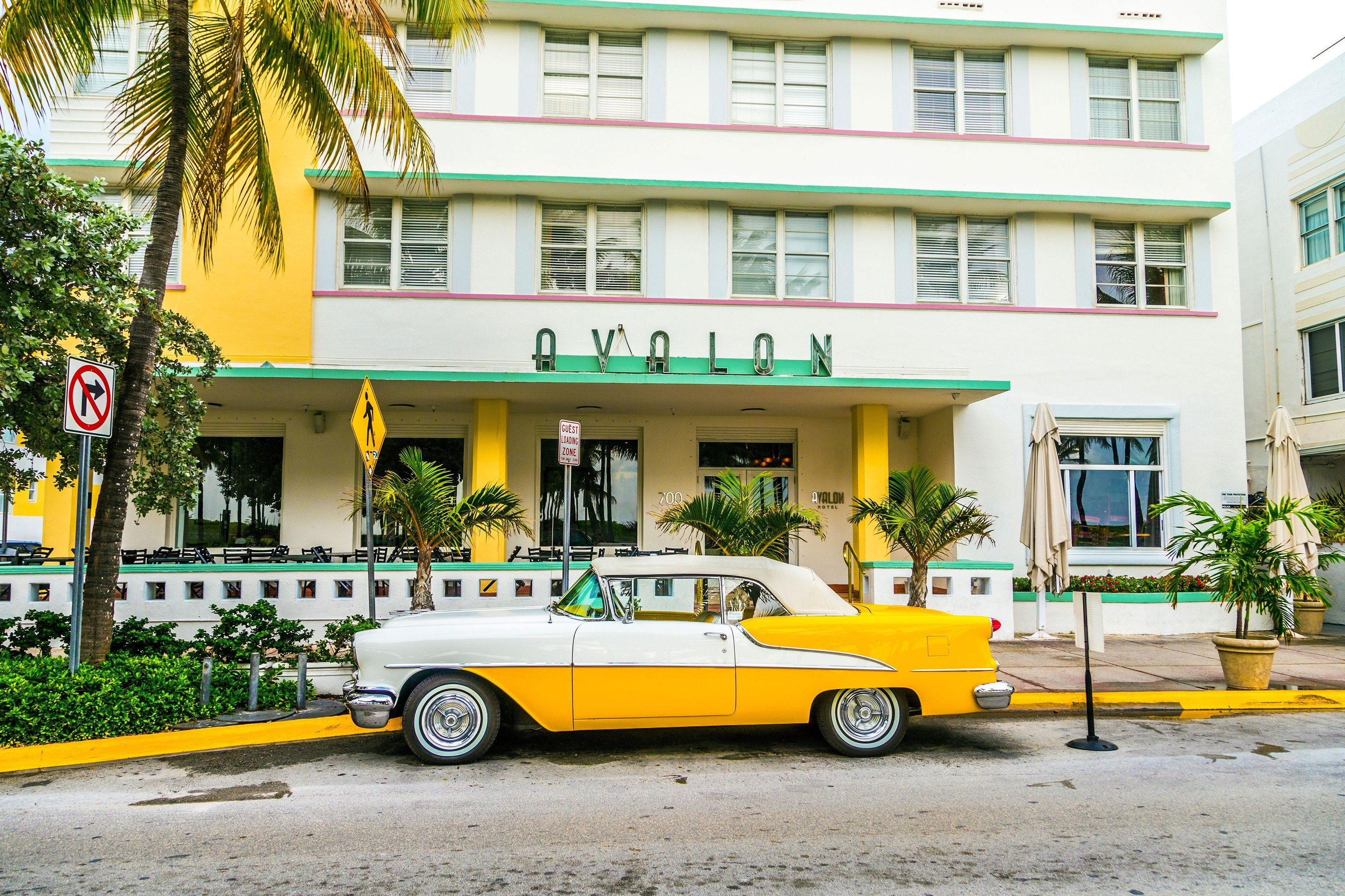 Offbeat building yellow car vehicle parked road neighbourhood street automobile make infrastructure taxi