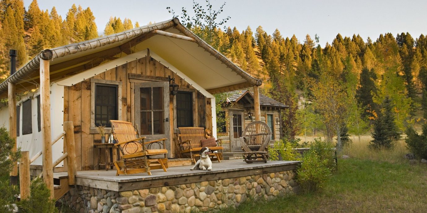 Glamping Hotels Luxury Travel Montana Outdoors + Adventure Trip Ideas Weekend Getaways outdoor grass sky tree building log cabin house property home estate cottage hut real estate old outdoor structure backyard farmhouse Villa shack