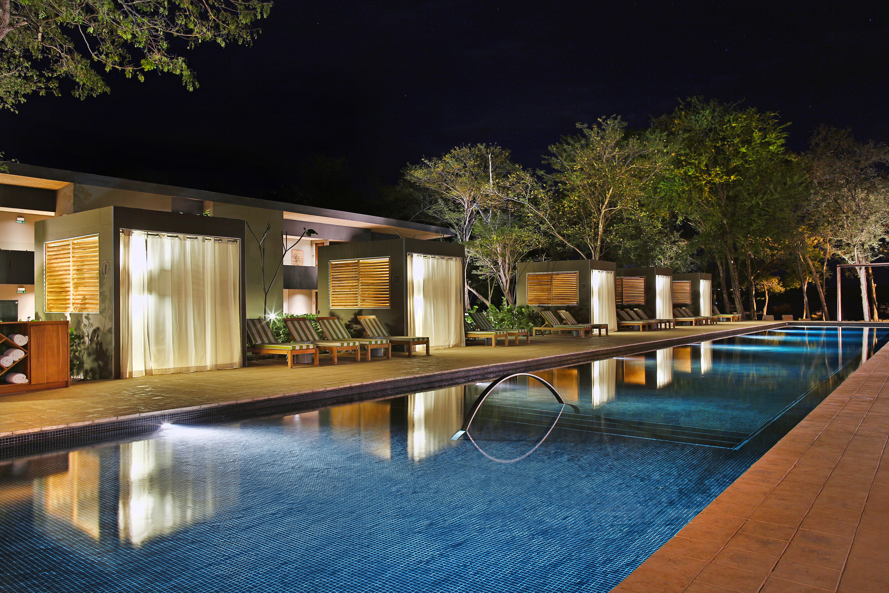 Beachfront Boutique Elegant Hip Hotels Patio Pool Waterfront tree outdoor swimming pool property estate house home Architecture reflecting pool backyard mansion reflection lighting landscape lighting condominium Villa real estate Courtyard Resort