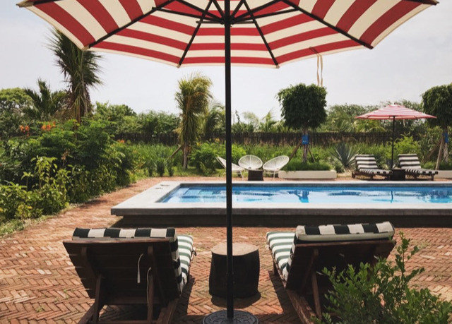 umbrella ground tree accessory sky property swimming pool Resort leisure outdoor furniture sunlounger lawn shade outdoor structure Patio Villa hacienda set sunny day