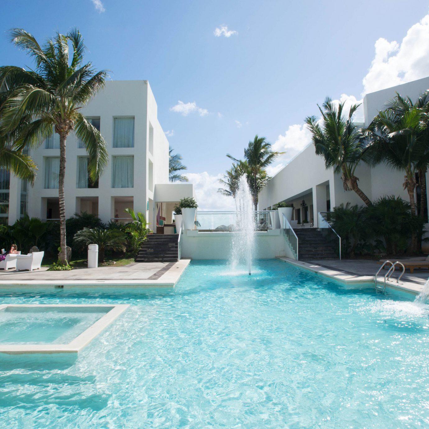 tree sky Pool water swimming pool property Resort leisure condominium caribbean Villa water sport resort town swimming mansion blue