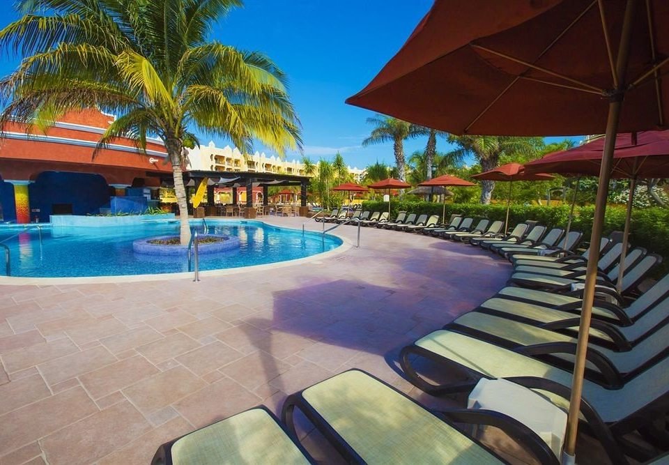 umbrella tree chair swimming pool leisure Resort property Pool Villa lawn caribbean hacienda Water park palm lined shade empty accessory colorful set